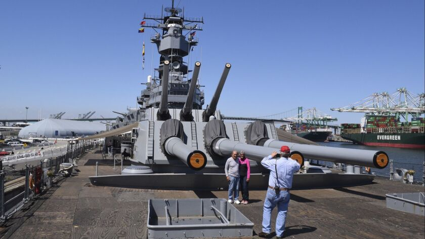 Aboard the battleship USS Iowa, visitors enjoy a view of the ship's iconic 16-inch guns and surrounding San Pedro.
