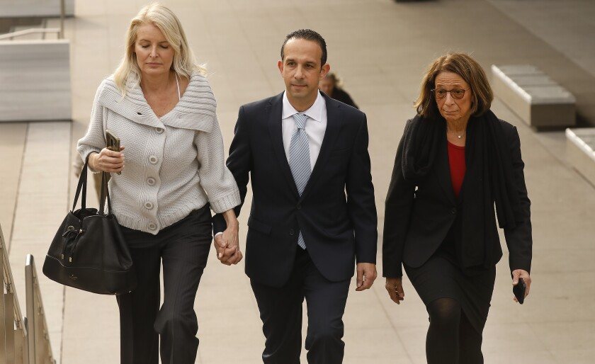Former Los Angeles City Councilman Mitch Englander walks with his wife and attorney