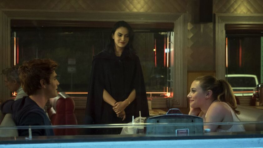 "Archie (KJ Apa) and Betty (Lili Reinhart) meet Veronica (Camila Mendes) for the first time in the new CW series ""Riverdale."""