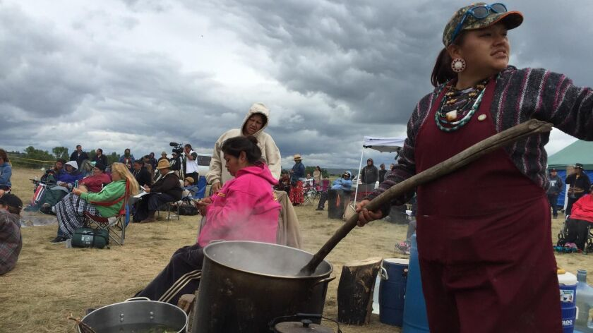 Nantinki Young, known as Tink, stirs soup for protesters gathered along the banks of the Cannonball River.