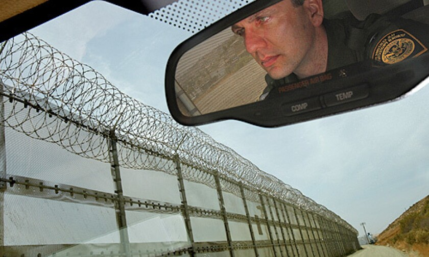 U.S. Border Patrol agent Richard Smith drives Wednesday along a section of the border fence in San Ysidro that was recently topped with razor wire.