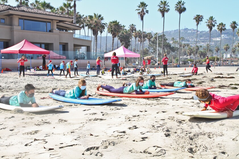 Students at Surf Diva's surf school in La Jolla must wear masks while on land.