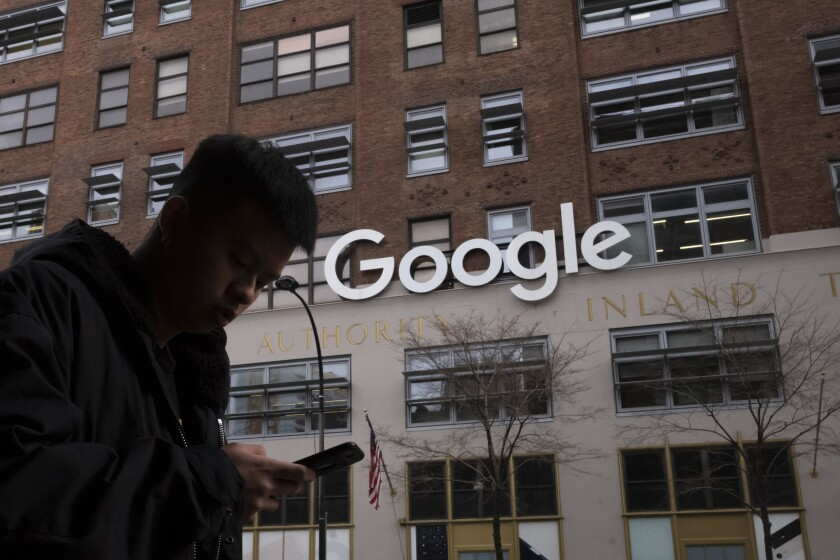 FILE - In this Dec. 17, 2018, file photo a man using a mobile phone walks past Google offices in New York. Google is closing the internal studio tasked with developing games for its Stadia cloud-gaming service, a move that raises questions about the future of its Stadia service itself. Google launched Stadia in November 2019 as a cloud-based gaming service, in deliberate contrast to pricey video-game consoles. But Google said Monday, Feb. 1, 2021 it will no longer invest in creating its own games for the service beyond any planned, near-term titles. (AP Photo/Mark Lennihan, File)
