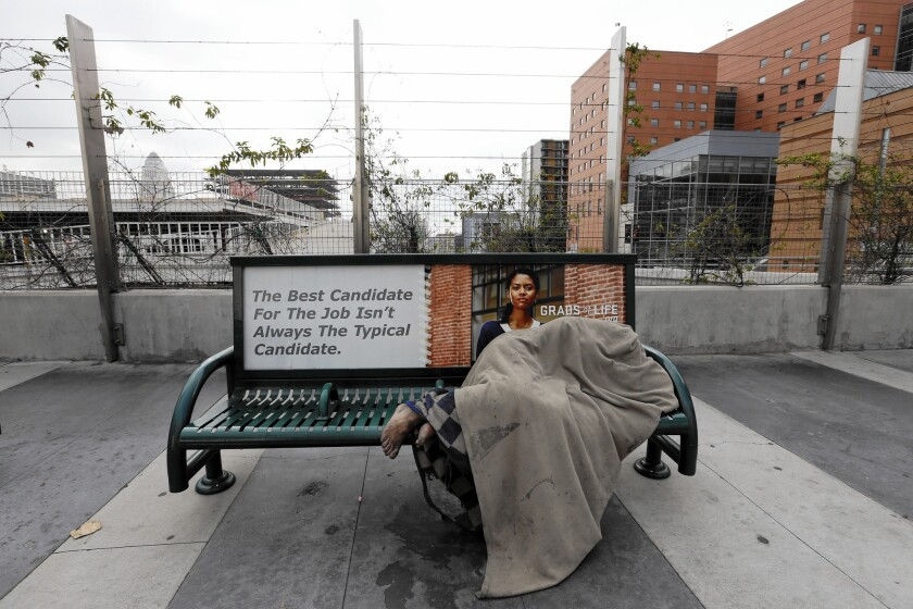 A homeless person sleeps beneath a blanket on a bus bench in downtown Los Angeles