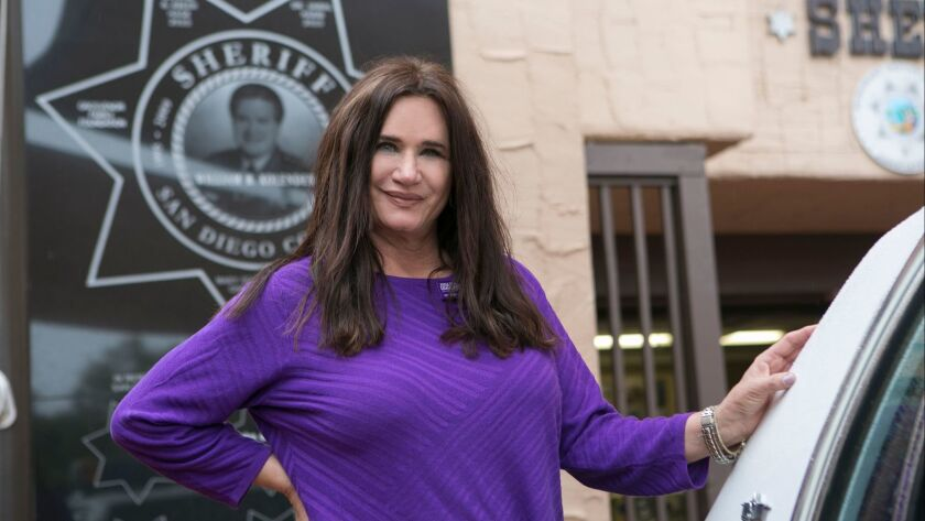 Randi Kolender-Hock of Del Mar, an advocate for Alzheimer's research, stands in front of a wall plaque honoring her late father at the William B. Kolender Sheriff's Museum in Old Town San Diego.