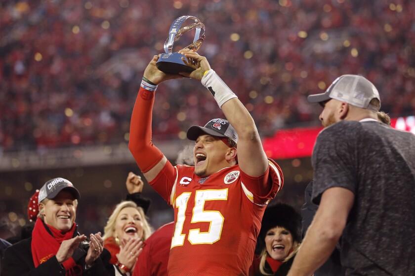 Kansas City quarterback Patrick Mahomes holds up the Lamar Hunt Trophy.