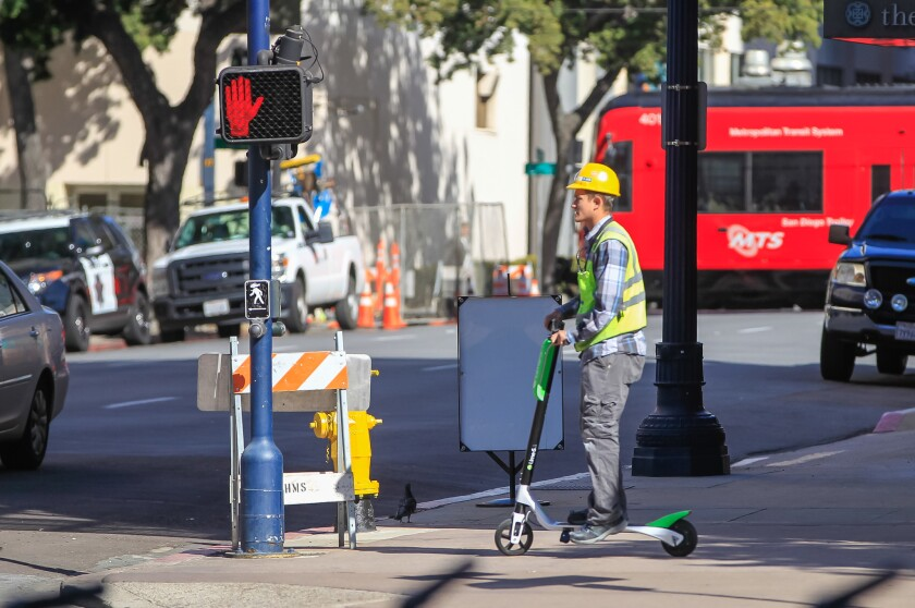 A person rides a LimeBike scooter along Broadway in San Diego.