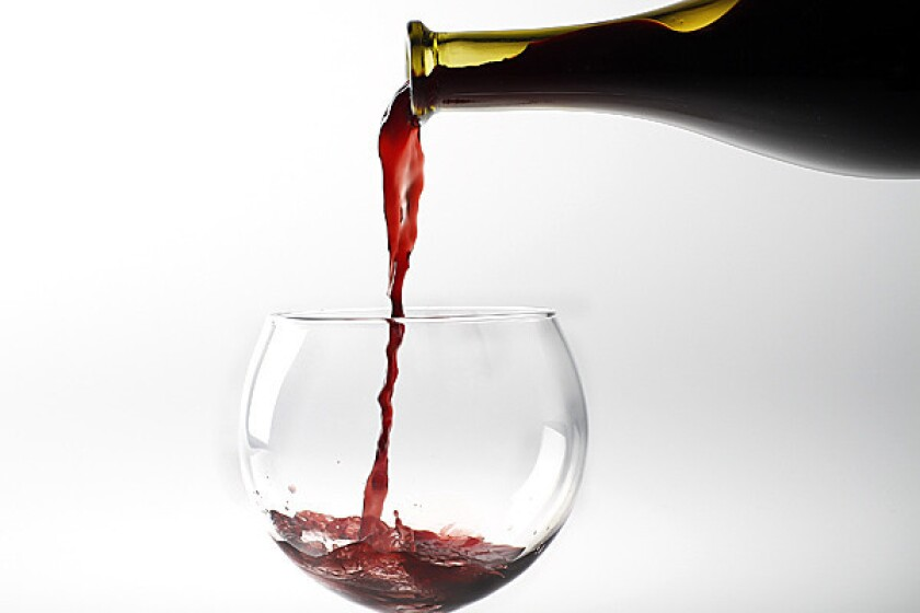 Red wine is poured from a bottle.