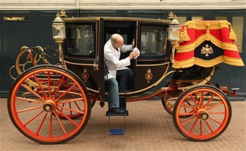 Carriage restorer, Dave Evans, cleans the Glass Coach at the Royal Mews in central London, Monday March 21, 2011. The coach, which was built in 1881, and is traditionally used by Royal brides to travel on their wedding day, will be used to carry Prince William and Kate Middleton in the event of bad weather on their wedding day on Friday, April 29, 2011. Should the weather be good on the day then the 1902 State Landau carriage will be used instead. (AP Photo/Dominic Lipinski, Pool)