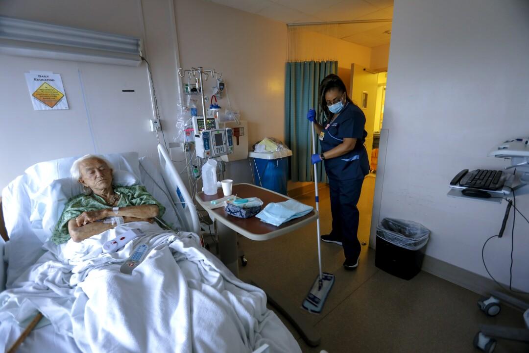 En el Centro Médico de San Diego, Connie Wright limpia la habitación del paciente Bob Longdyke mientras hace sus rondas normales.