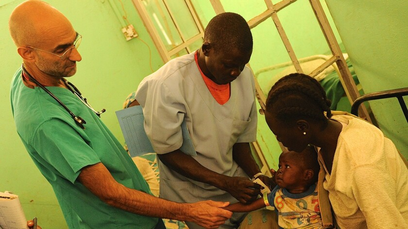 """Dr. Tom Catena (left) and his patients in a scene from """"The Heart of Nuba."""" Credit: Kenneth Carlson"""