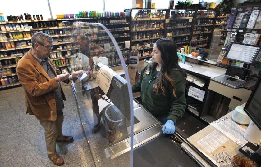 Barons Market installed sneeze shields to separate customers from clerks.