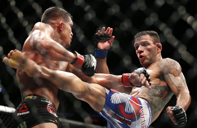 Rafael Dos Anjos, right, delivers a kick to Anthony Pettis on his way to winning the lightweight title during UFC 185 in Dallas on March 15, 2015.