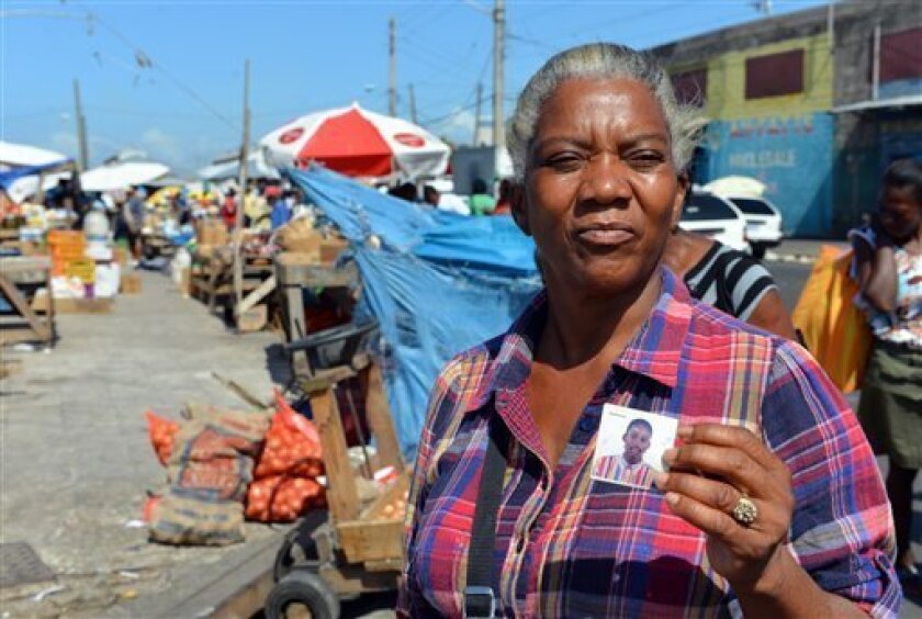 In this April 13, 2013 photo, Claudette Johnson shows a photo of her slain son Tyrone Johnson, who was 21 when he was killed, as she poses for a photo at the market in West Kingston, Jamaica.  Johnson still has a hard time sleeping at night a decade after her son was fatally shot in a confrontation