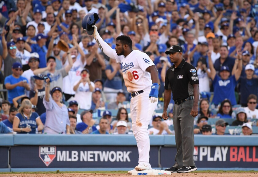 Yasiel Puig #66 of the Los Angeles Dodgers reacts after stealing third base as third base umpire Alan Porter #54 looks on during the eighth inning of Game Five of the National League Championship Series against the Milwaukee Brewers at Dodger Stadium on October 17, 2018 in Los Angeles, California. Puig was sent back to second base after home plate umpire Jim Wolf ruled the batter interfered with the throw to third base.