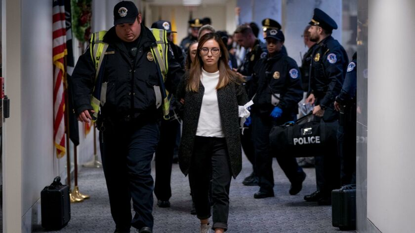 A woman is arrested after protesting in the Senate offices of Sen. Dianne Feinstein, D-Calif., to de