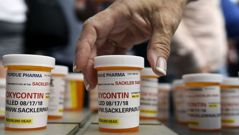 People who have lost loved ones to OxyContin and opioid overdoses leave pill bottles in protest outside the headquarters of Purdue Pharma, which is owned by the Sackler family, in 2018.