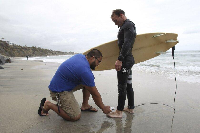 Student Alvin Padilla takes the temperature of surfer James Petracca's foot