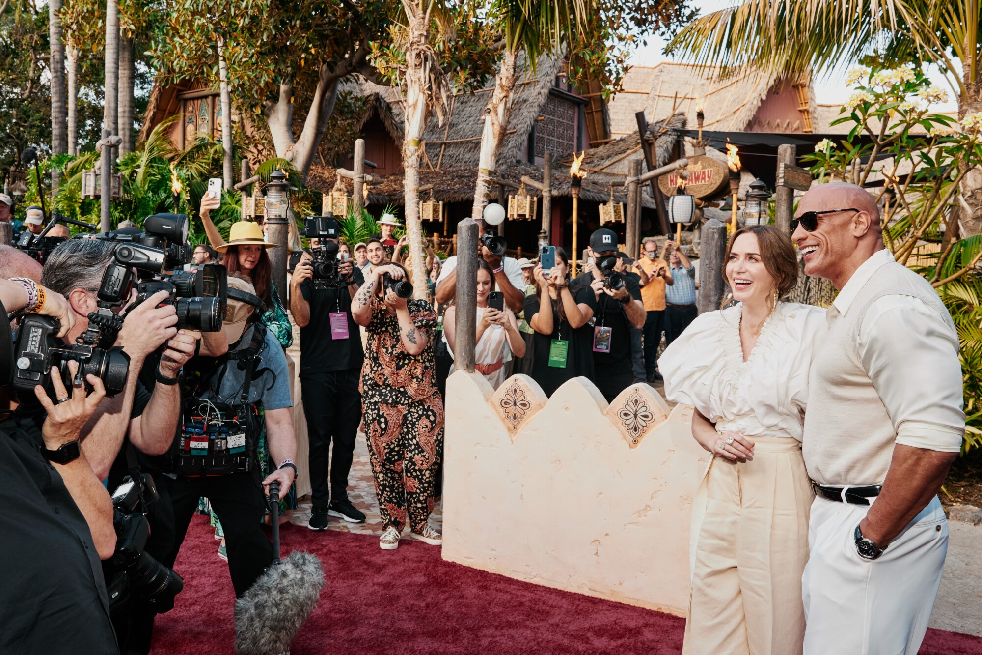 Emily Blunt and Dwayne Johnson exit the Jungle Cruise ride and stand for photographers on the red carpet.