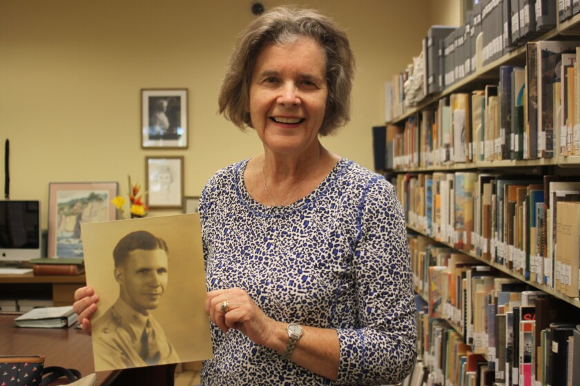 Betty Little with a photo of her father, who was deployed immediately after Pearl Harbor, which she wanted digitally scanned.
