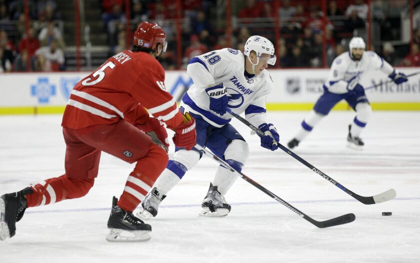 Carolina Hurricanes' Ron Hainsey, left, defends against Tampa Bay Lightning's Ondrej Palat (18), of the Czech Republic, during the first period of an NHL hockey game in Raleigh, N.C., Sunday, Nov. 1, 2015. (AP Photo/Gerry Broome)