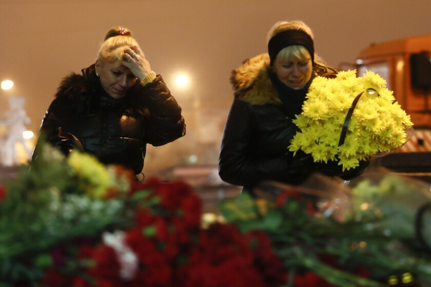 A woman weeps as she places flowers outside the railway station in the Russian city of Volgograd, one of two sites in the city targeted by suspected suicide bombers.