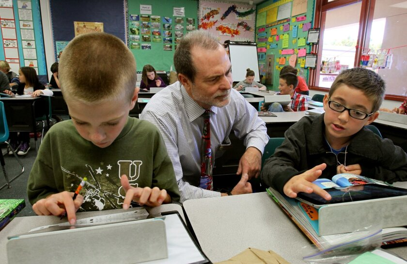In this file photo, Timothy Baird, superintendent of the Encinitas Union School District, watches students use their school-issued iPads. At left is Andrew Frandsen and at right is Noah Kesslin.