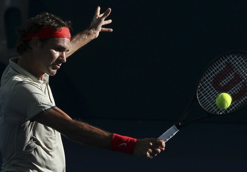 Roger Federer of Switzerland plays a shot in his semifinal match against Jeremy Chardy of France during the Brisbane International tennis tournament in Brisbane, Australia, Saturday, Jan. 4, 2014. (AP Photo/Tertius Pickard)