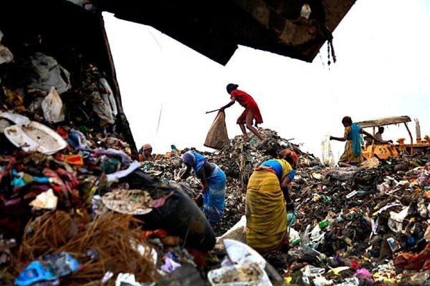 "Rag pickers hunt through the 100-foot-high ""trash mountain"" at New Delhi's Ghazipur landfill."