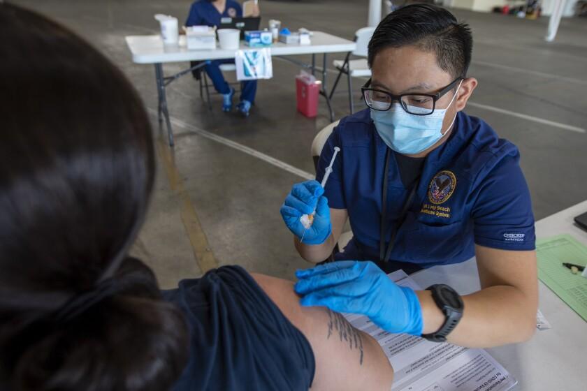 A nurse administers a COVID-19 vaccine