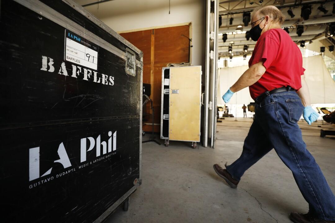 A masked man strides past L.A. Phil equipment