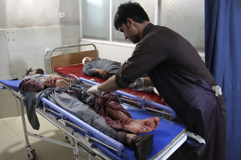 A wounded man is treated at a hospital Sunday after a suicide car bomb and gun battle in Afghanistan's Nangarhar province.