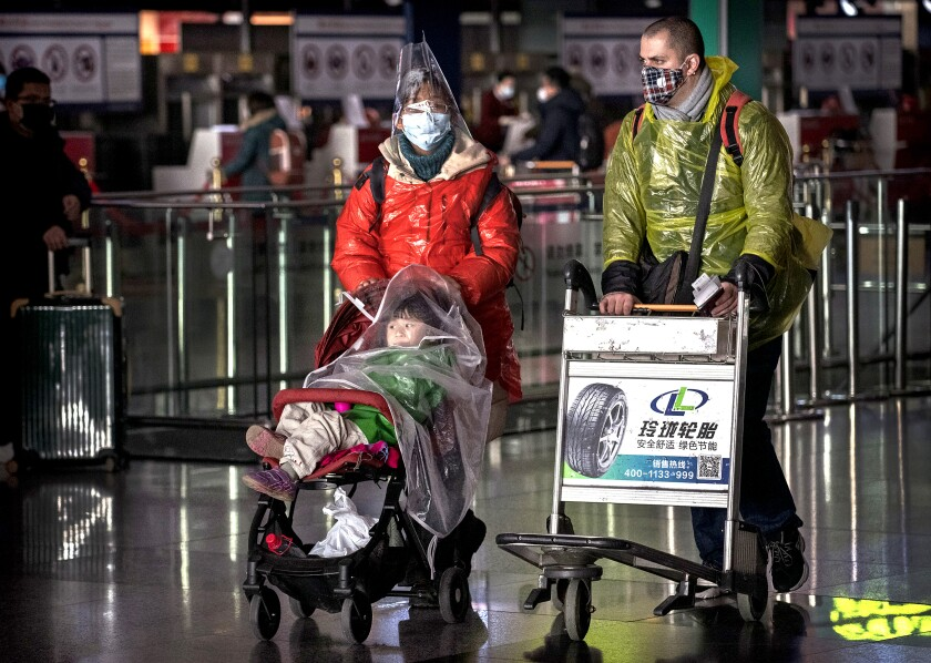 A family wears protective plastic covers and masks as they walk after checking in to a flight at Beijing Capital Airport.