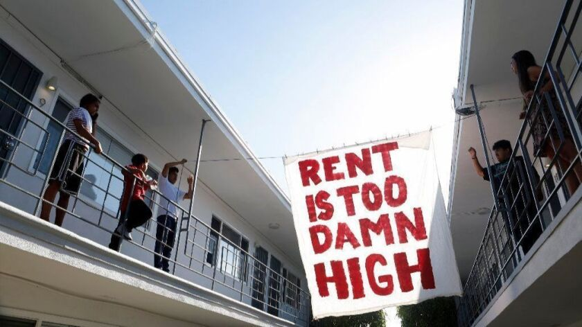 Organizers with a local tenants' rights group hang a protest sign in the courtyard of an apartment building in Long Beach last June.