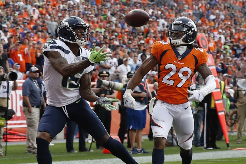 FILE - In this Sept. 9, 2018, file photo, Seattle Seahawks wide receiver Brandon Marshall, left, hauls in a touchdown pass in the end zone as Denver Broncos defensive back Bradley Roby (29) watches during the second half of an NFL football game in Denver. Marshall's transition to life after football following the 2018 season has gone smoothly. But none of it would be possible if Marshall hadn't realized he needed help nearly a decade ago to deal with isolation and bouts of depression. (AP Photo/David Zalubowski, File)