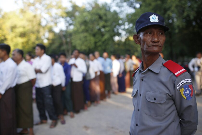 Police officer stands guard as voters queue up outside a polling station in Mandalay, Myanmar, Sunday, Nov. 8, 2015. Myanmar voted Sunday in historic elections that will test whether popular mandate will help loosen the military's longstanding hold on power even if opposition leader Aung San Suu Ky
