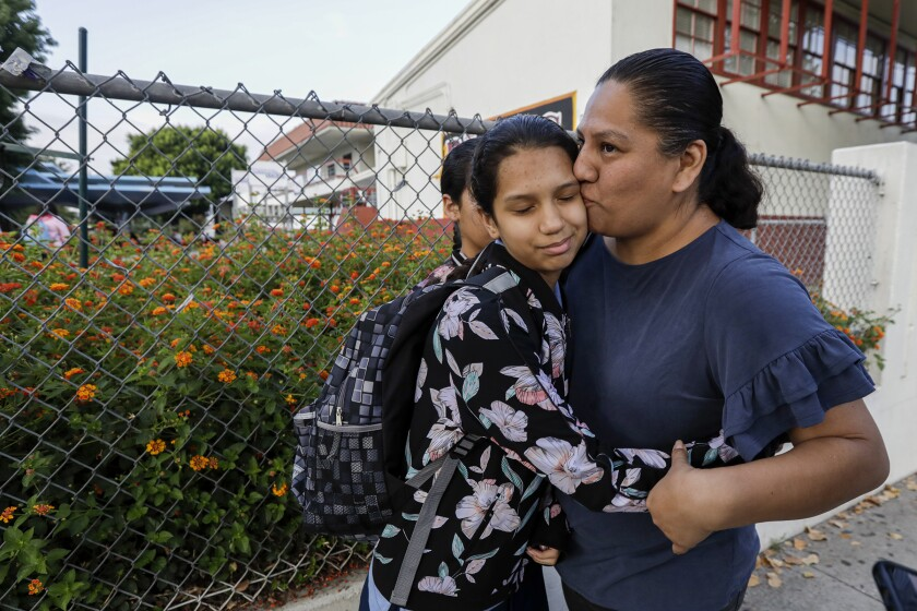Nereyda Bautista drops her daughter, April Bauitista, off at Hollenbeck Middle School in Boyle Heights. A student was shot in the jaw on August, 27 at the school, possibly struck by a bullet fired from off campus.