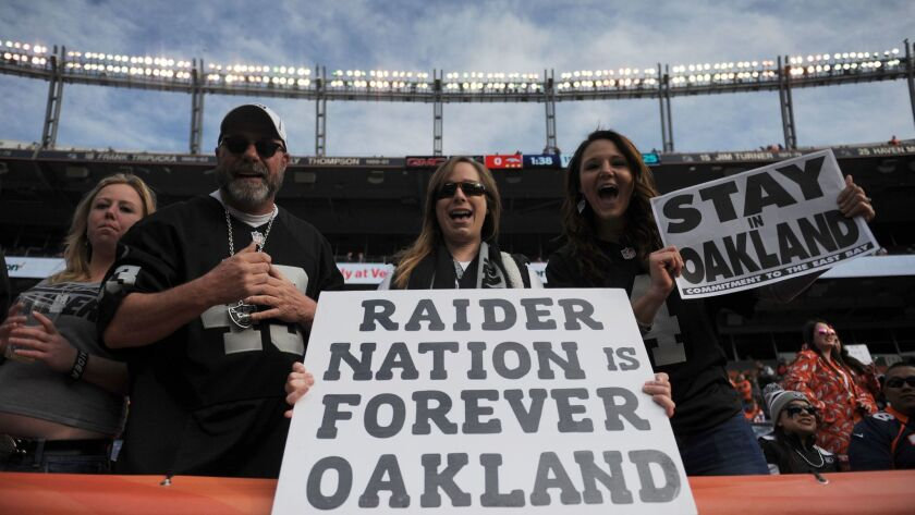 Oakland Raiders fans hold signs before a game in Denver on Jan. 1.