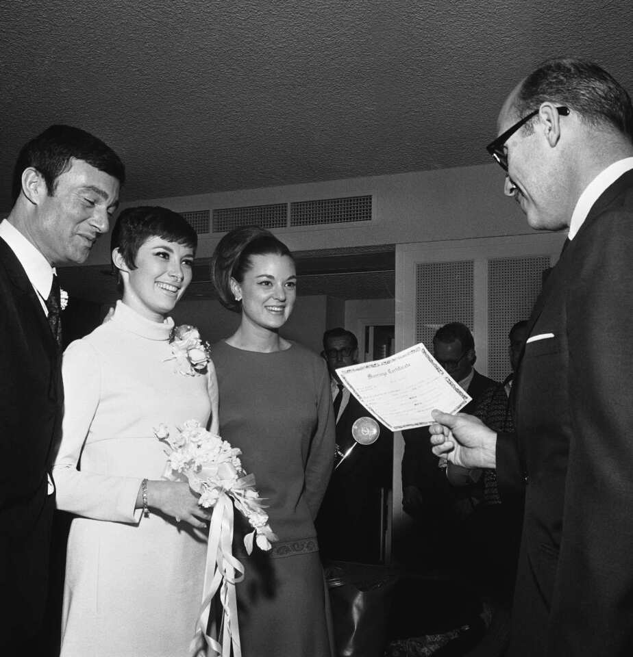 Justice of the Peace Herman Fisher, right, begins the wedding ceremony of Vidal Sassoon and his second wife, Beverly Adams, at the Hotel Sahara in Las Vegas on Feb. 16, 1967. Pictured are Sassoon, left, Adams and Cathy McElman, matron of honor.
