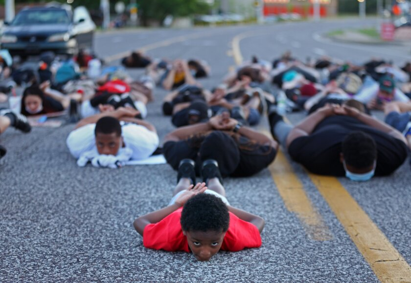 Six-year-old Blue Scott, of Florissant, Mo.,assumes a prone position on Sunday, June 7, 2020, as he participates with about 100 protesters in a die-in in the middle of Lindbergh Boulevard in front of the Florissant Police Station in Florissant, Mo. A suburban St. Louis police detective has been suspended after a video appears to show him hitting a man with a police SUV and then hitting the suspect at least twice while arresting him. Florissant Police Chief Tim Fagan has asked St. Louis County police and the FBI to investigate. (Christian Gooden/St. Louis Post-Dispatch via AP)