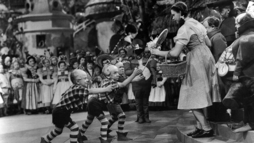 """Munchkin Jerry Maren (center), playing a Lollipop Guild Member, presents Judy Garland with a lollipop in the film 1939 film, """"The Wizard of Oz."""""""