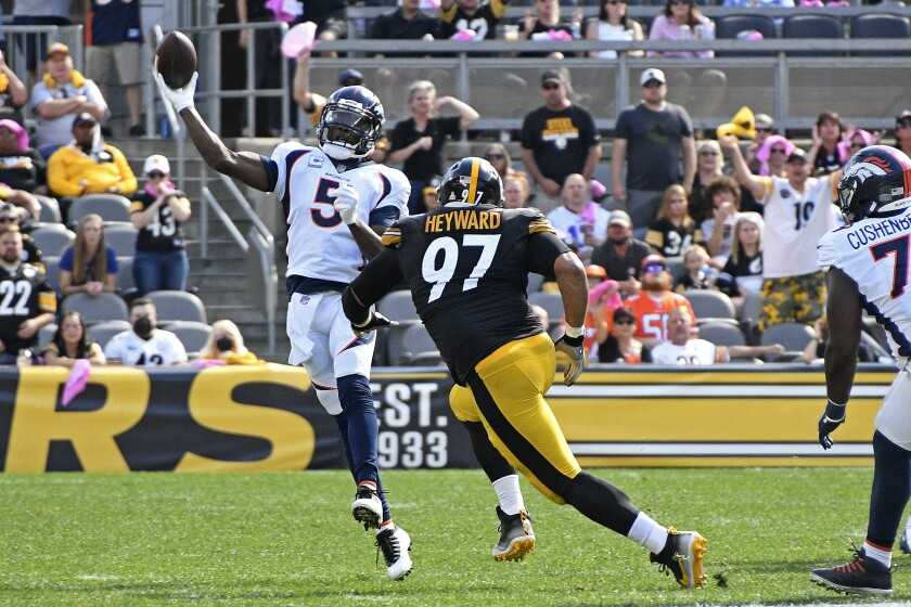 Denver Broncos quarterback Teddy Bridgewater (5) gets off a pass under pressure by Pittsburgh Steelers defensive end Cameron Heyward (97) during the first half of an NFL football game in Pittsburgh, Sunday, Oct. 10, 2021. (AP Photo/Don Wright)