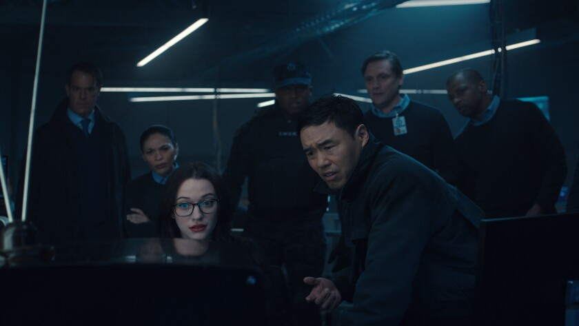 """Kat Dennings, Randall Park and others crowding around a TV set in """"WandaVision."""""""