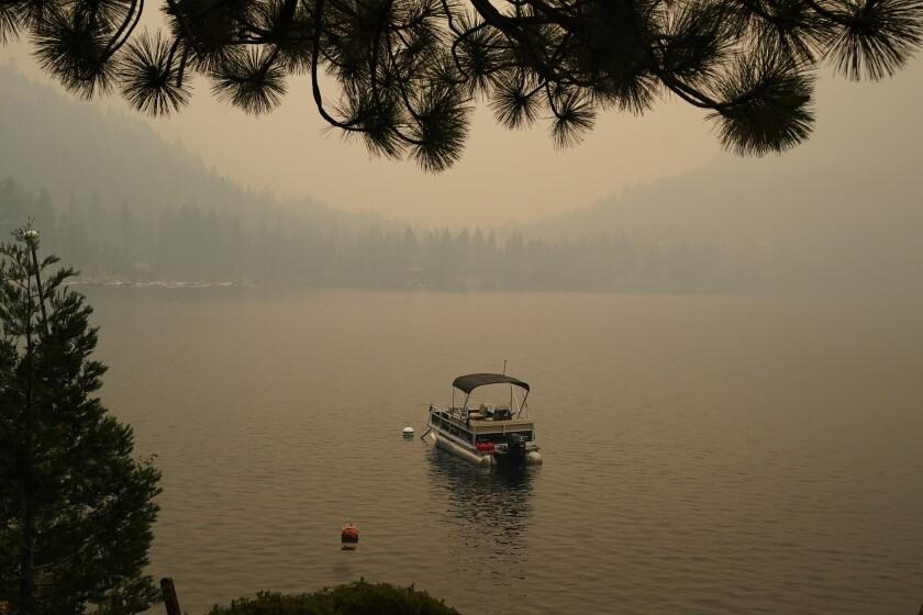 A boat on a lake amid smoke.