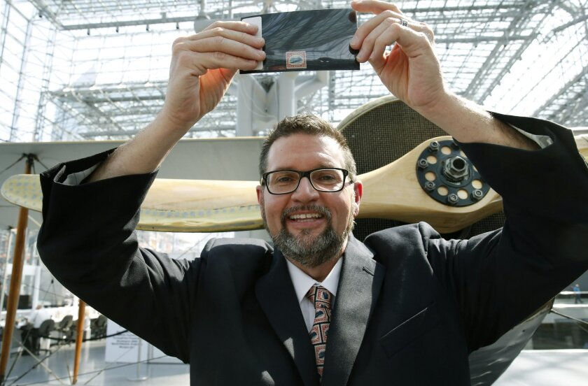 "American Philatelic Society executive director Scott D. English holds an ""Inverted Jenny,"" a 1918 stamp stolen in 1955, that is finally being returned to its rightful owner, featuring an airplane printed upside-down, after it was officially handed over during the World Stamp Show, Thursday, June 2,"