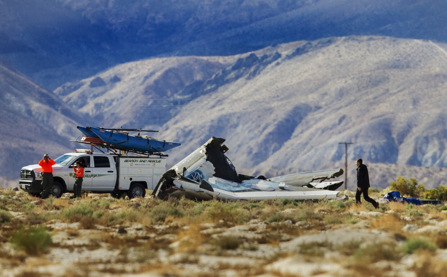 Kern County Sheriff officers keep watch as an investigator looks over the wreckage site of the Virgin Galactic SpaceShipTwo in Mojave.