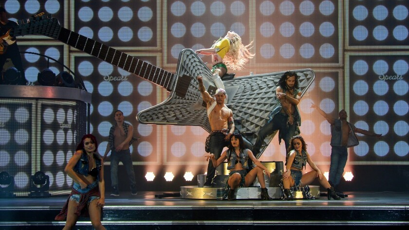 """With her popularity riding high, Britney Spears straddles a giant guitar during  her signature show """"Britney: Piece of Me"""" at Planet Hollywood."""
