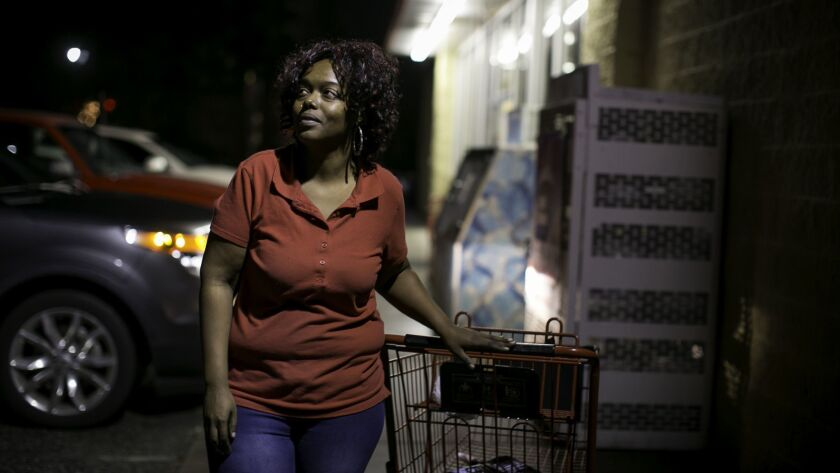 Jeneva Legions, 30, stands in front of the Bladenboro, N.C., Family Dollar where she works. She says