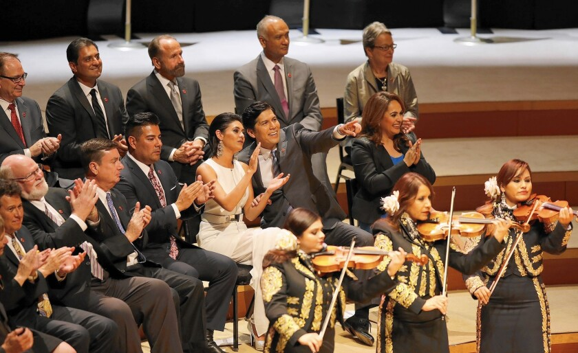 State Sen. Kevin de León of Los Angeles with daughter Lluvia Carrasco, point to friends during his inauguration as the 47th president pro tem of the California State Senate at the Walt Disney Concert Hall.
