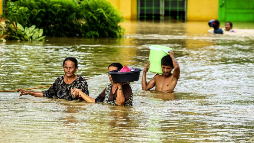 Residents wade through floodwater as they evacuate to a safer place in Kabacan, Cotabato, on the southern island of Mindanao.